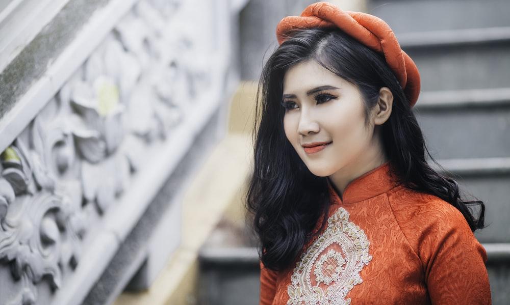 woman wearing red cheongsam top near stair