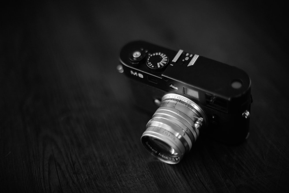black and gray camera on wooden surface