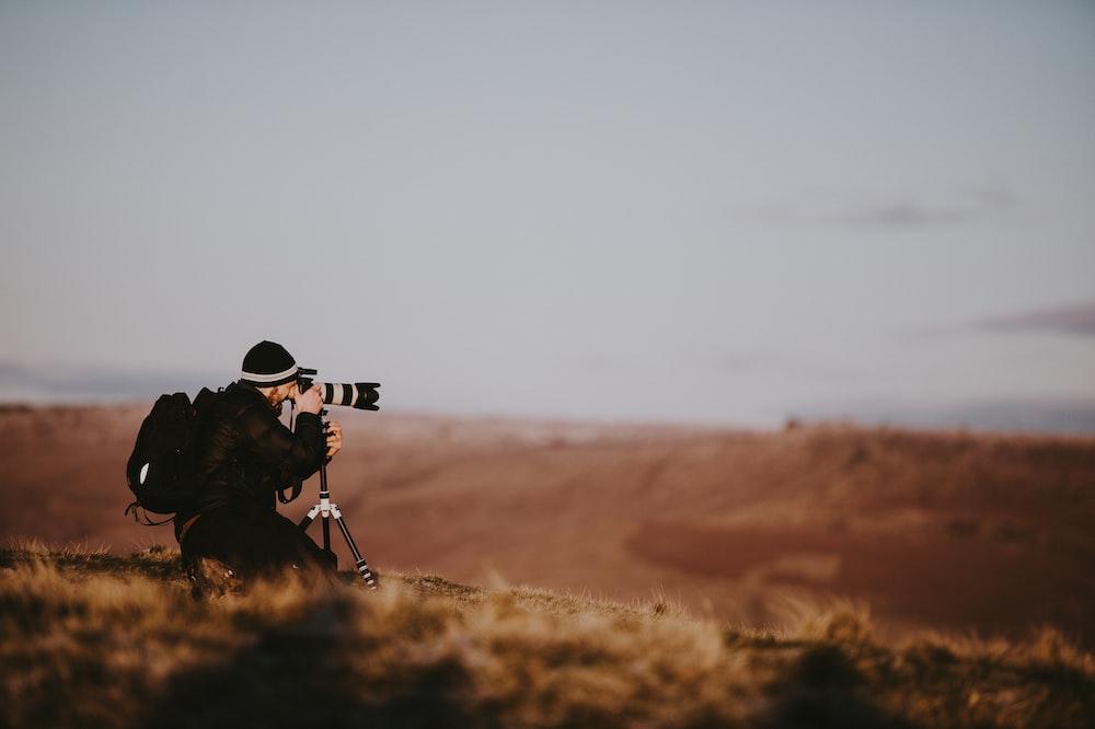 man using black DSLR camera during daytime