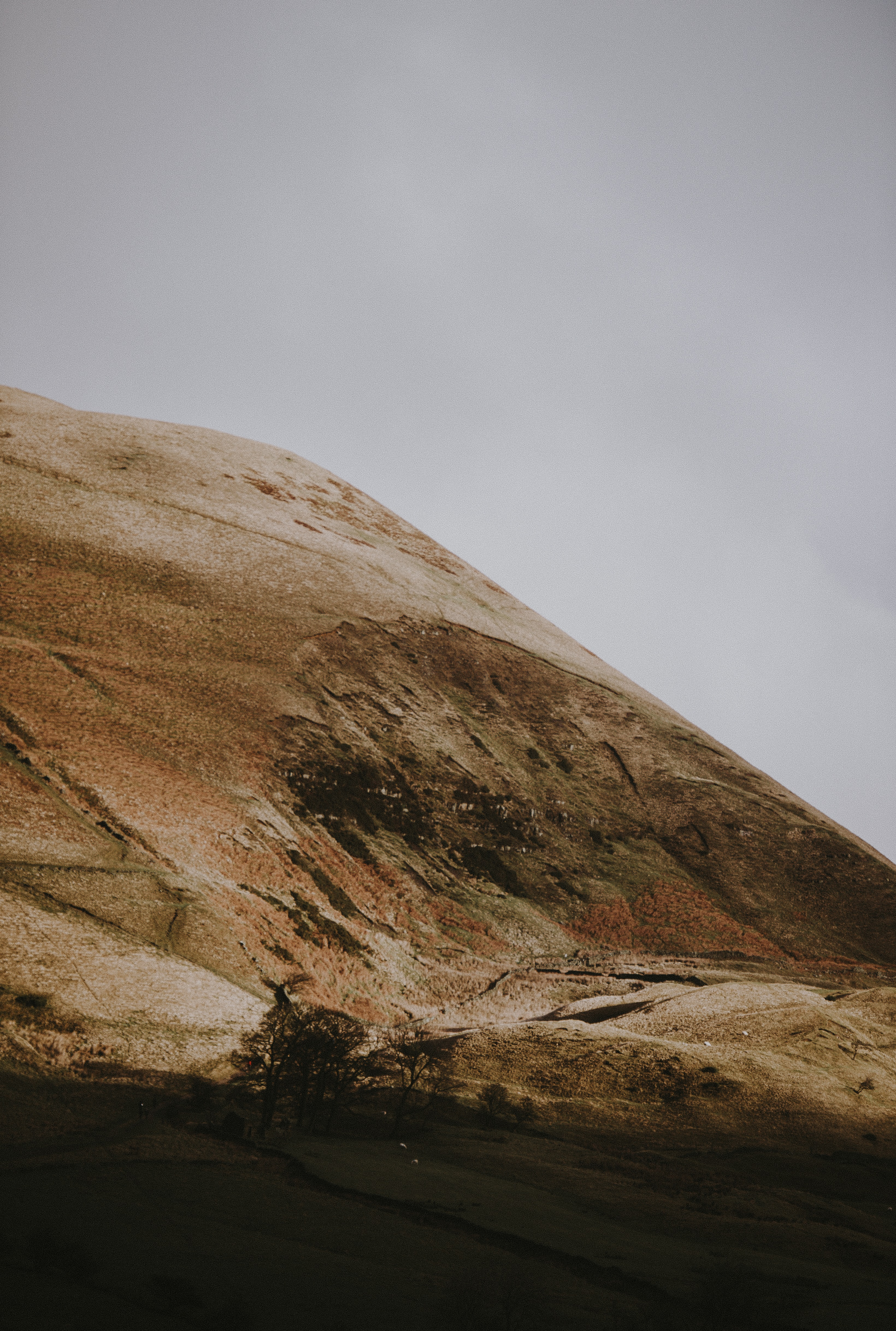 photo of brown mountain under gray clouds