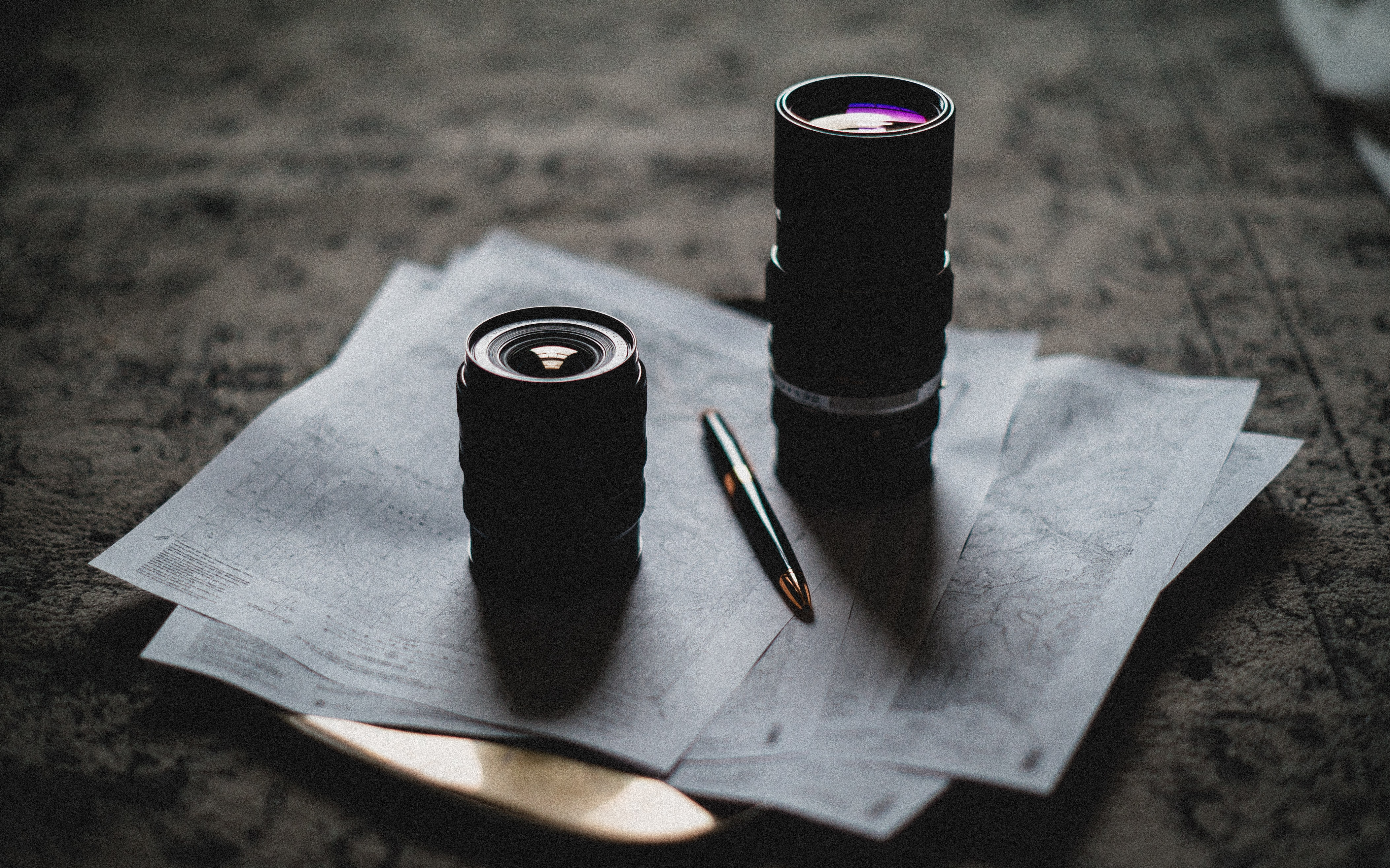 two camera lens on top of white printed papers and black and gold click pen