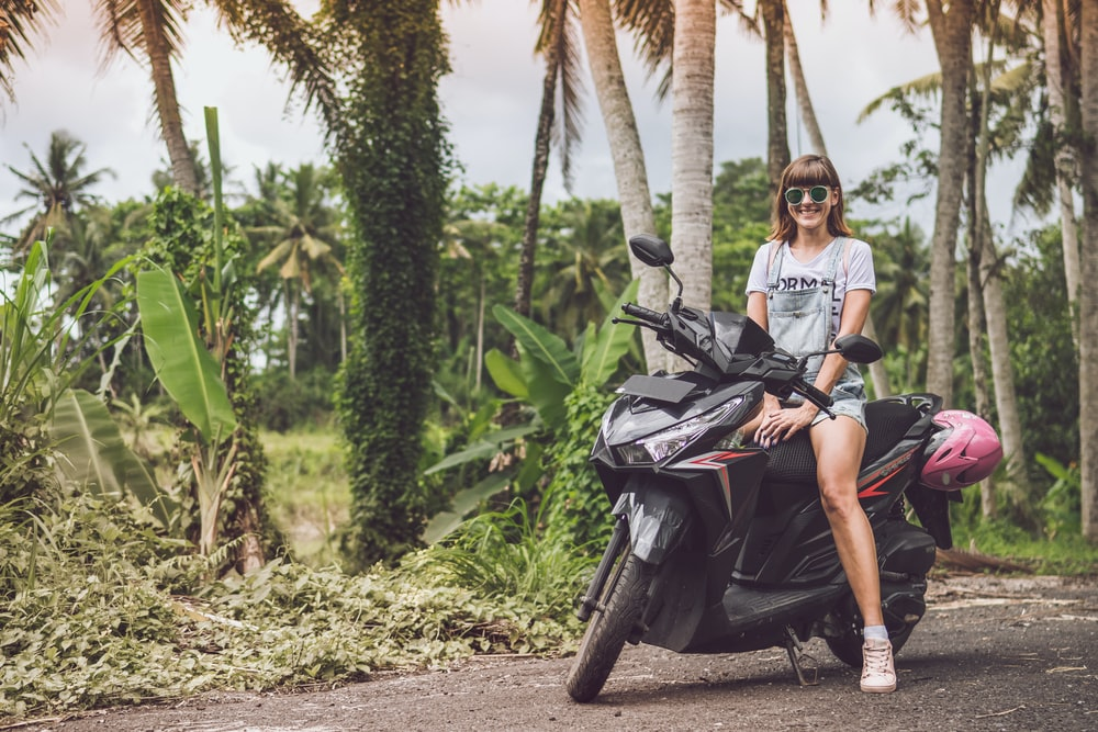 woman smiling on top of black motor scooter