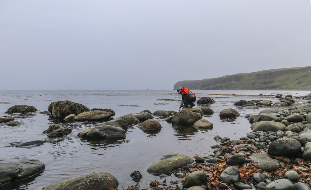 person crouching on rock boulder near body of water