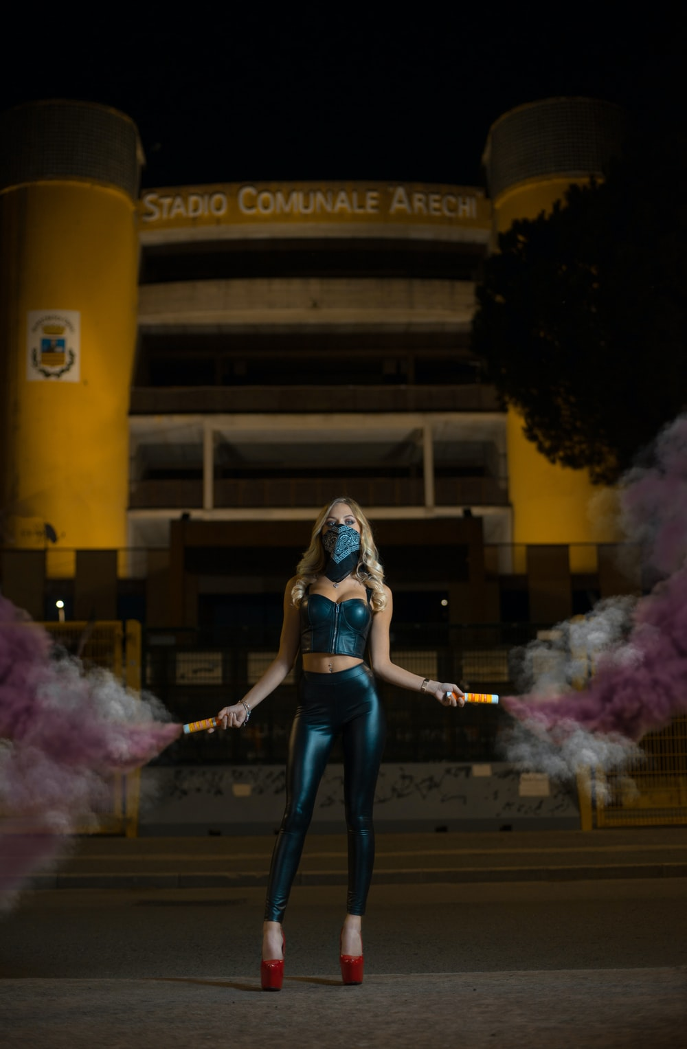 woman standing on pavement holding smoke bombs during night time