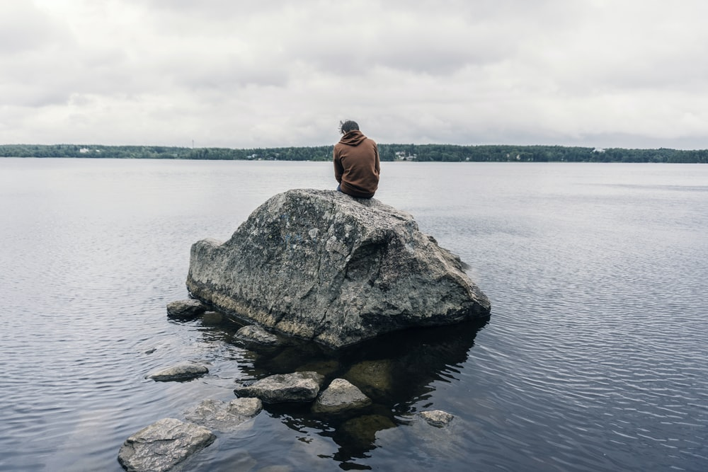 person sitting on rock surrounded by water