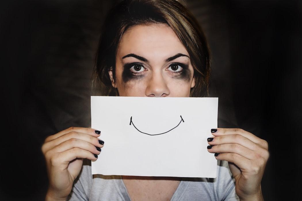 ragazza col trucco sbavato e un foglietto con sorriso disegnato davanti la bocca