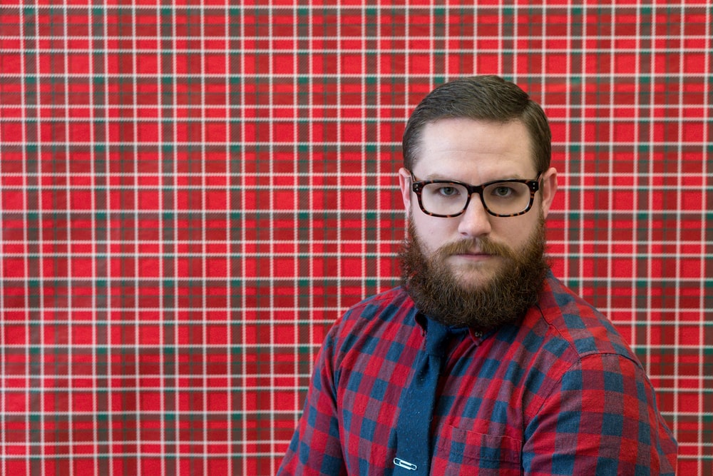 man wearing eyeglasses near red wall