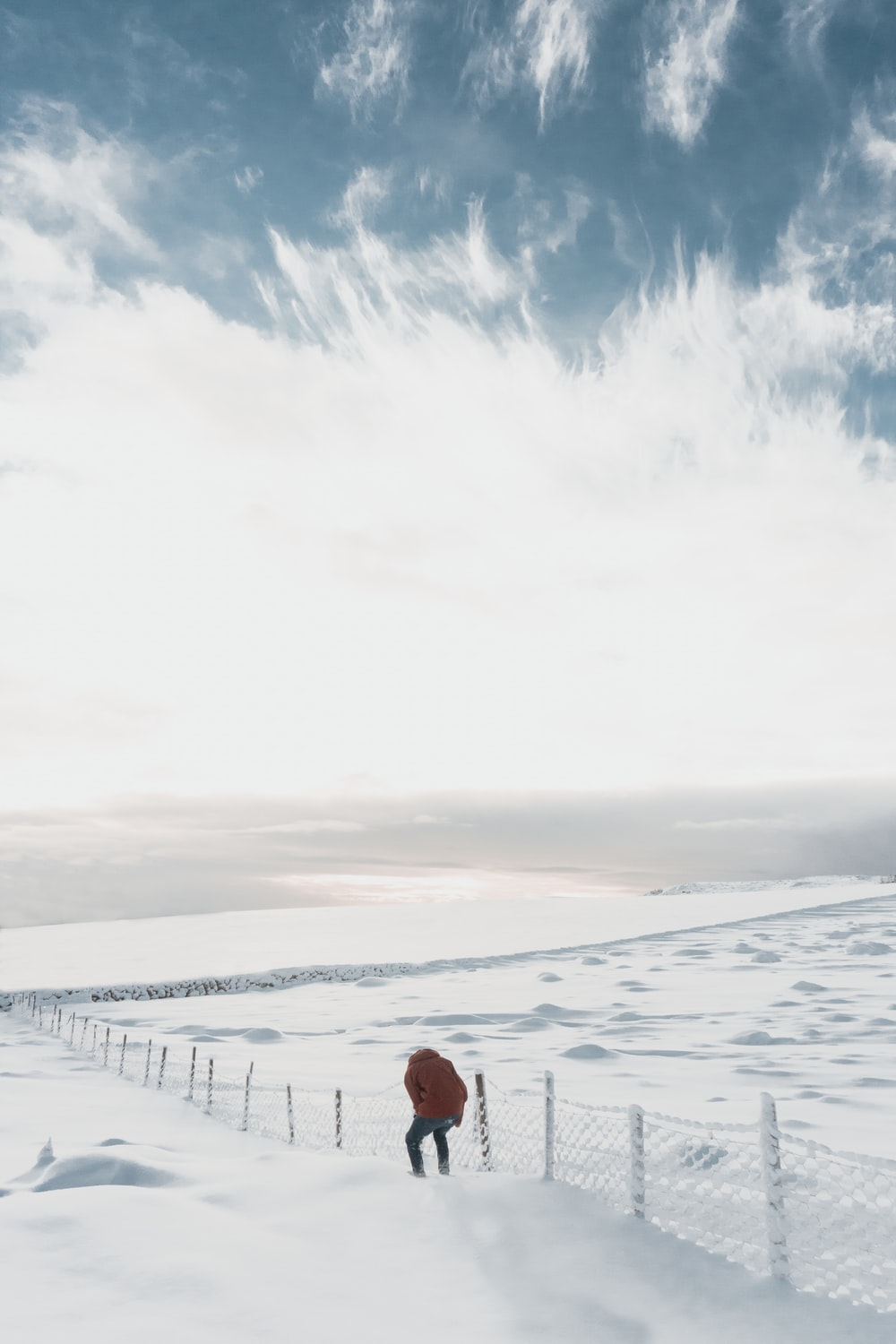 man beside white fence on snowfield