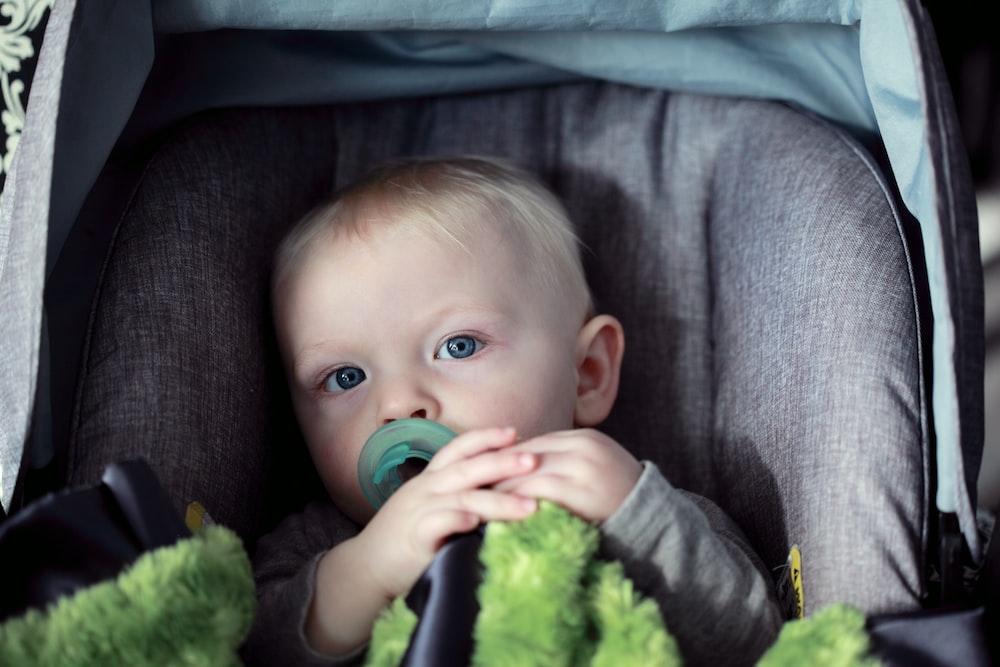 baby on gray stroller