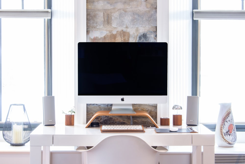 white iMac on top white desk