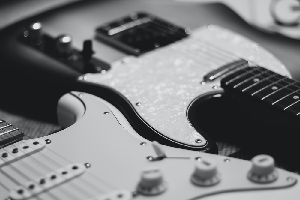 black and white photo of two stratocaster electric guitars