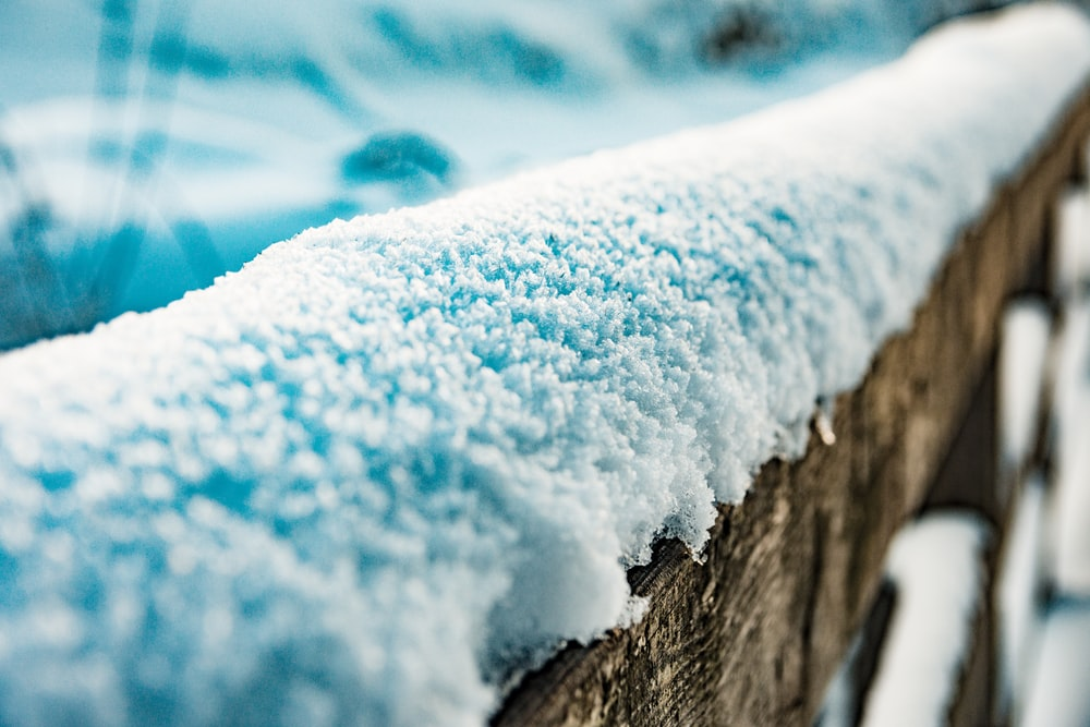 brown wooden fence covered by snow