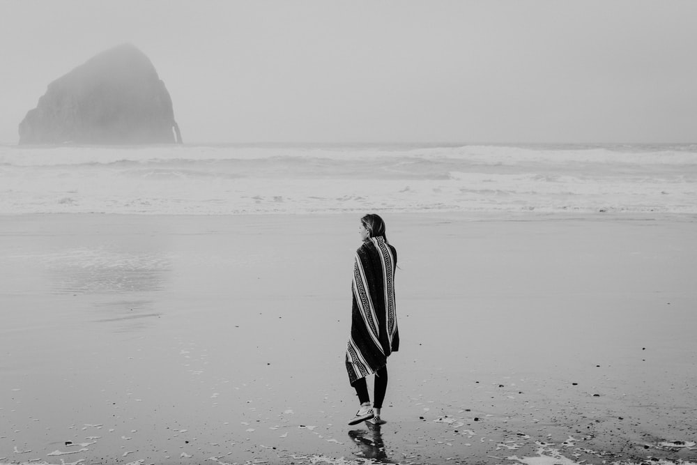grayscale photo of woman standing on shore