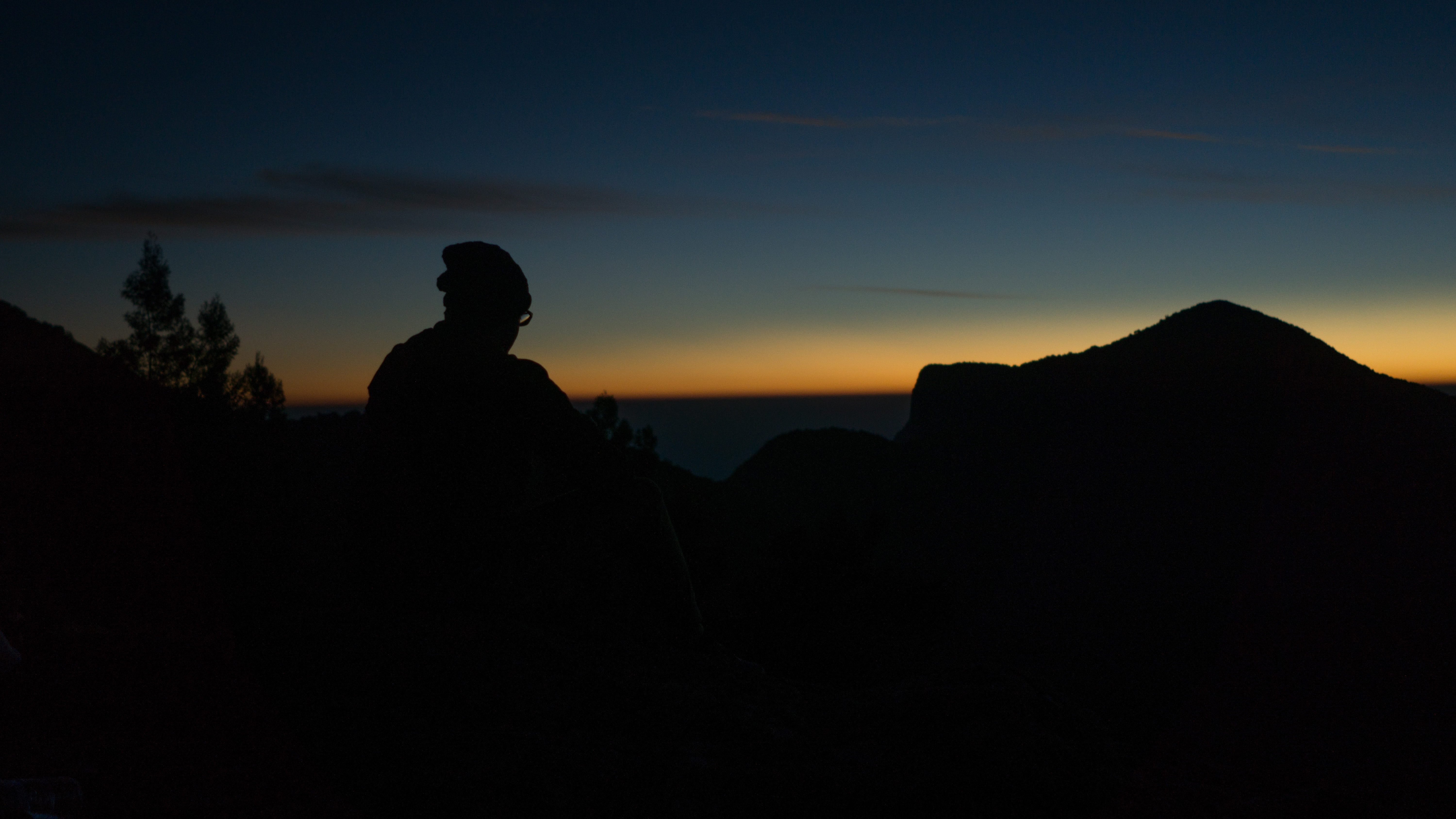 silhouette of person sitting during nighttime