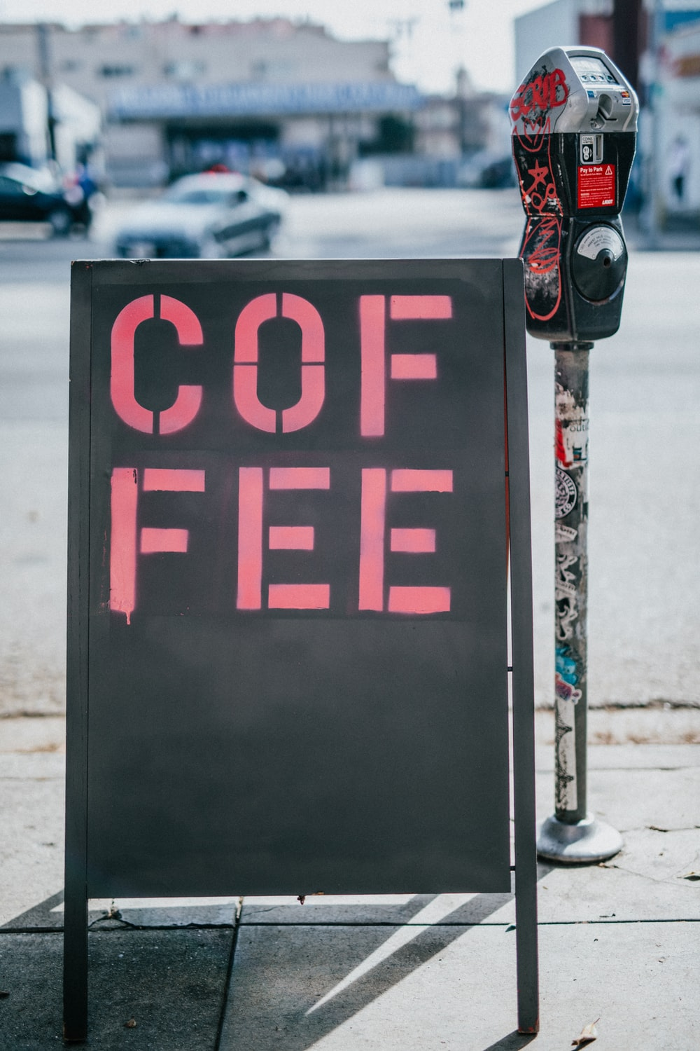 black freestanding signage with coffee print beside coin parking slot
