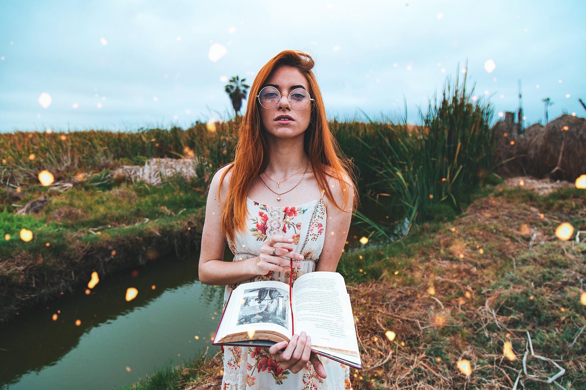 woman holding an open book near the creek