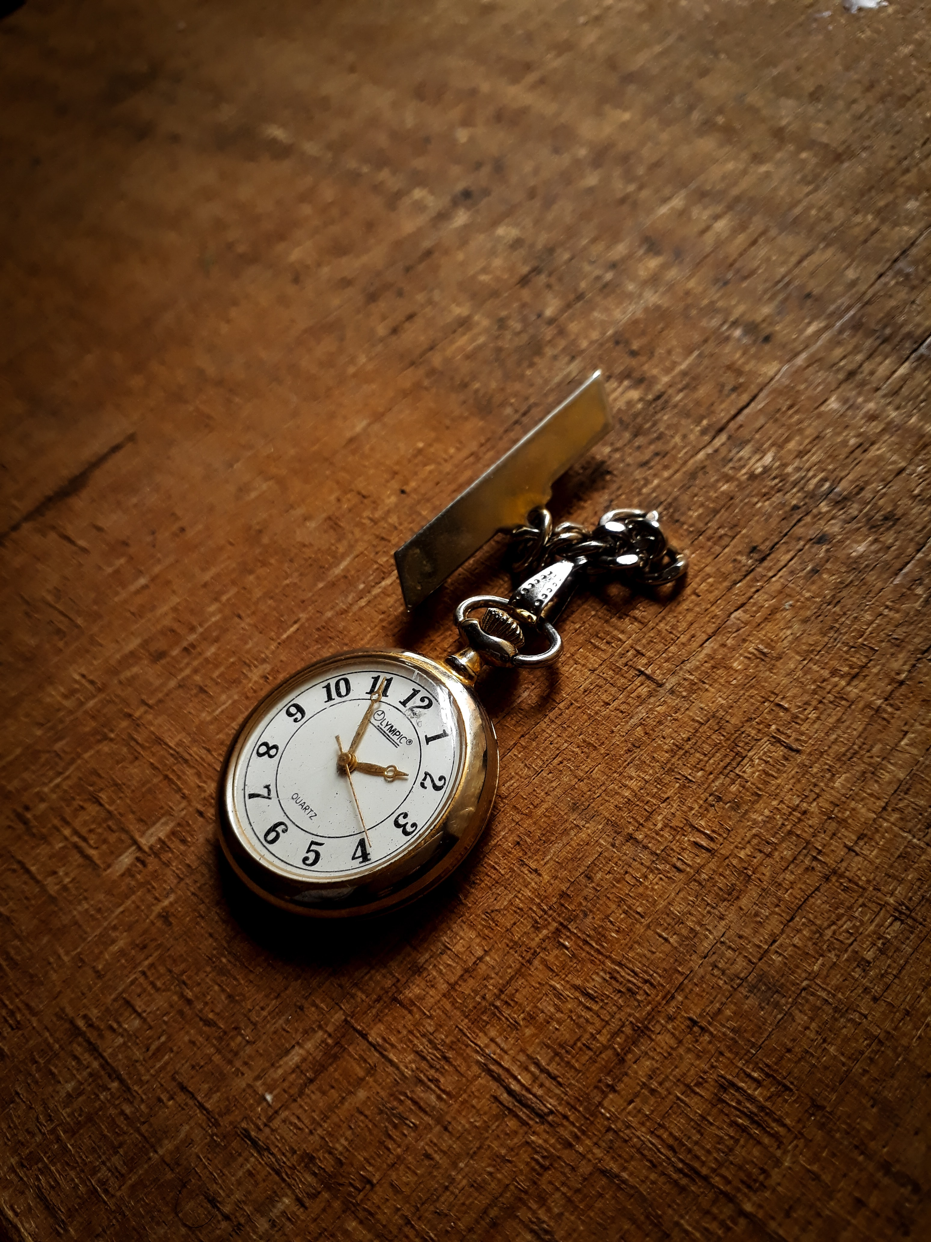 round gold-colored pocketwatch at 2:55