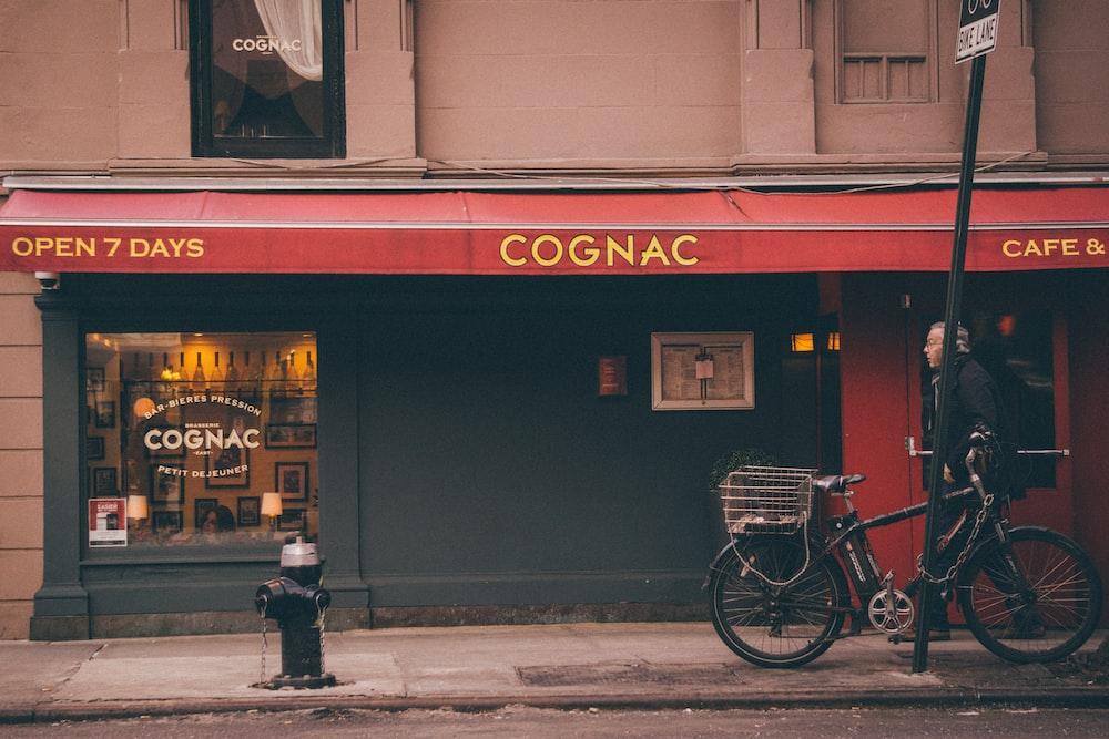 man walking in front of Cognac store