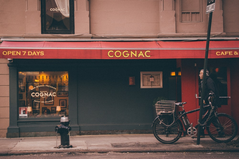man walking in front of Cognac store