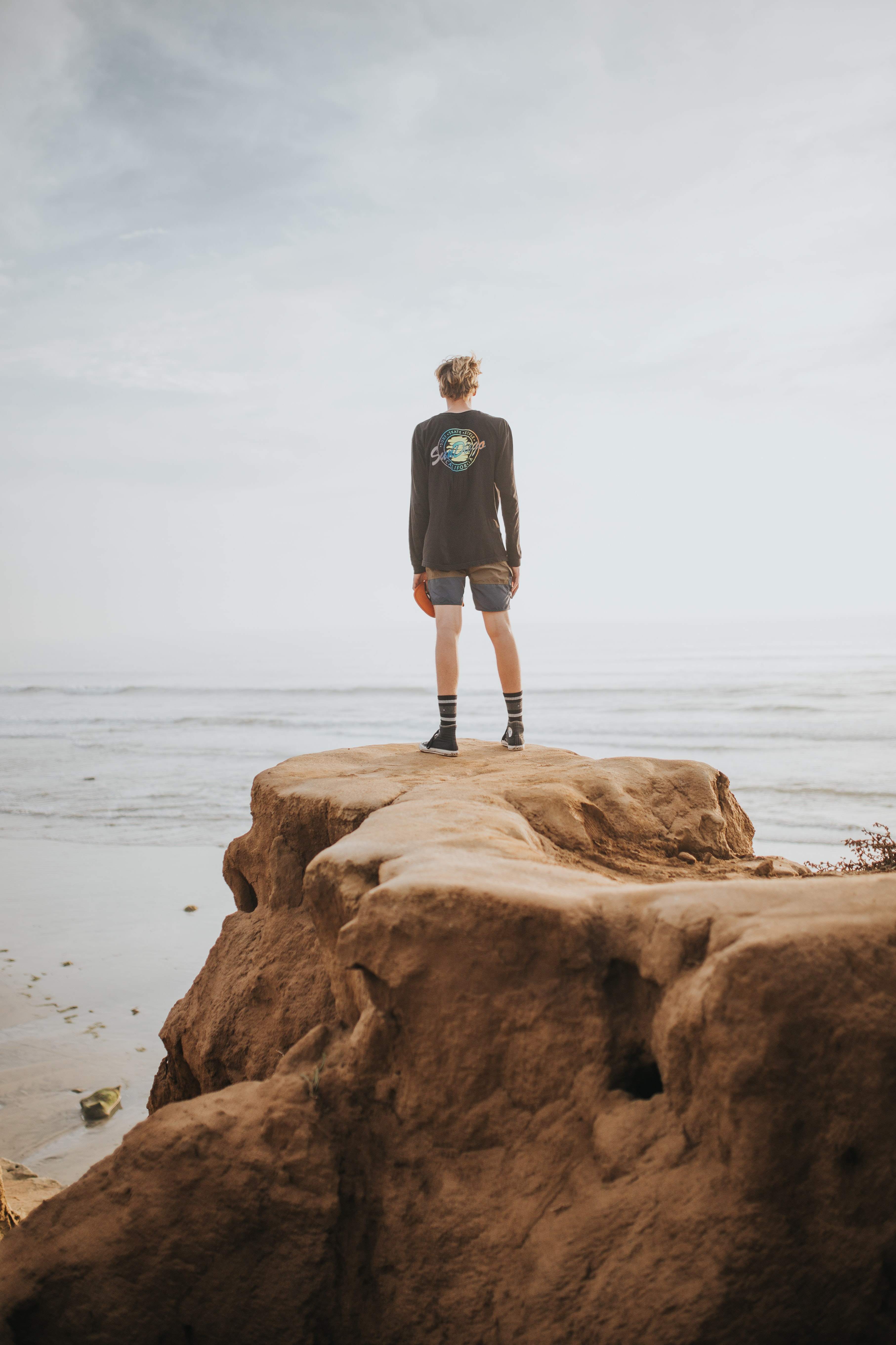 person standing on rock formation looking to sea during daytime