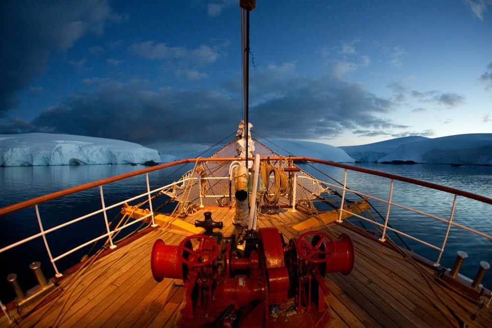 red and brown boat deck and iceberg at distance