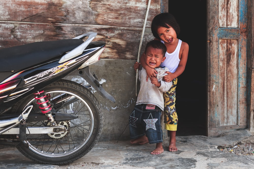 boy and girl standing near motorcycle
