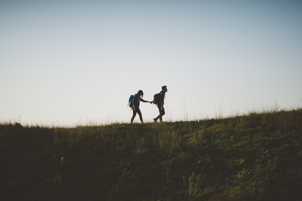 couple walking on hill while holding during daytime