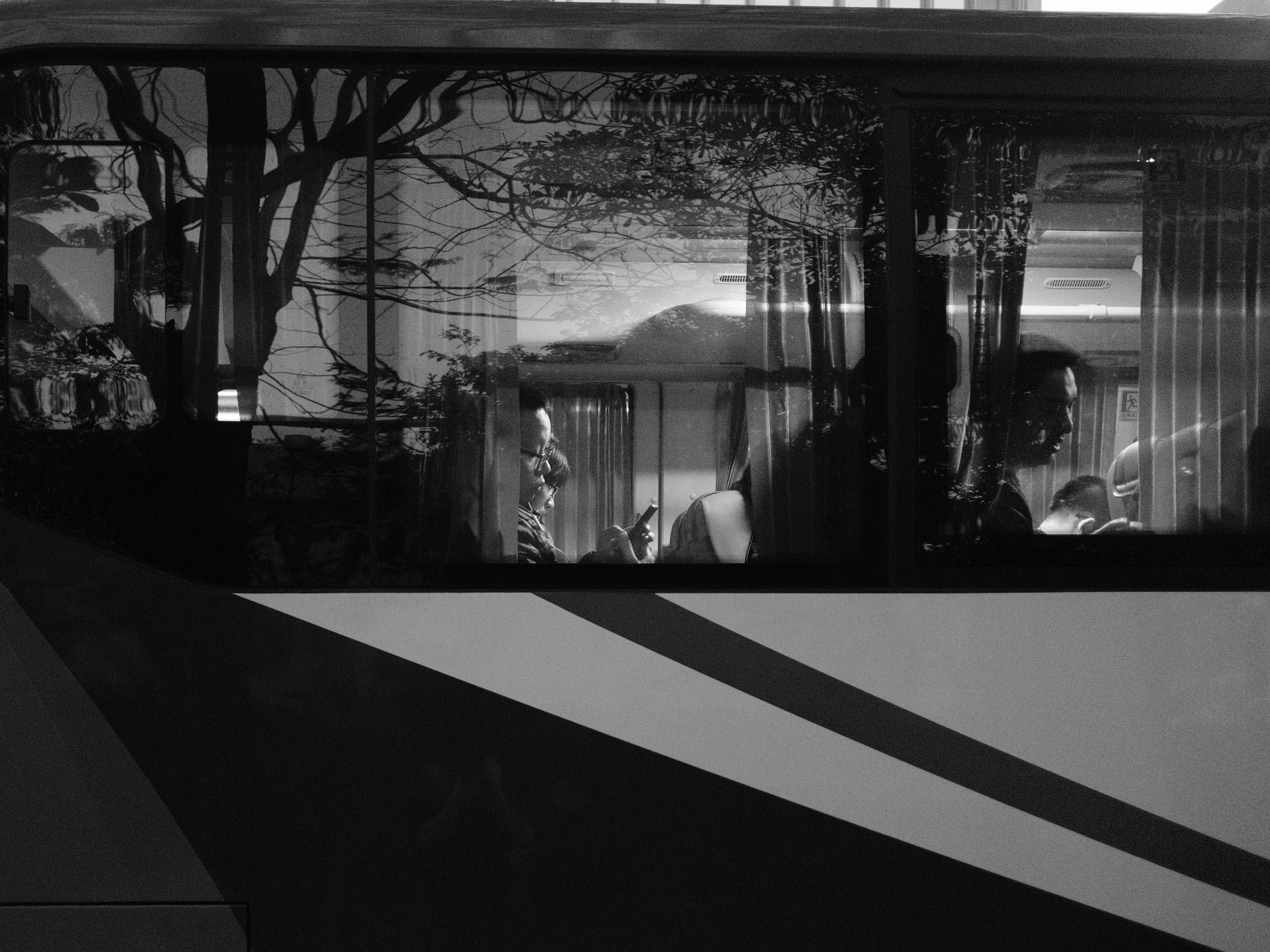 black and white photo of people riding bus