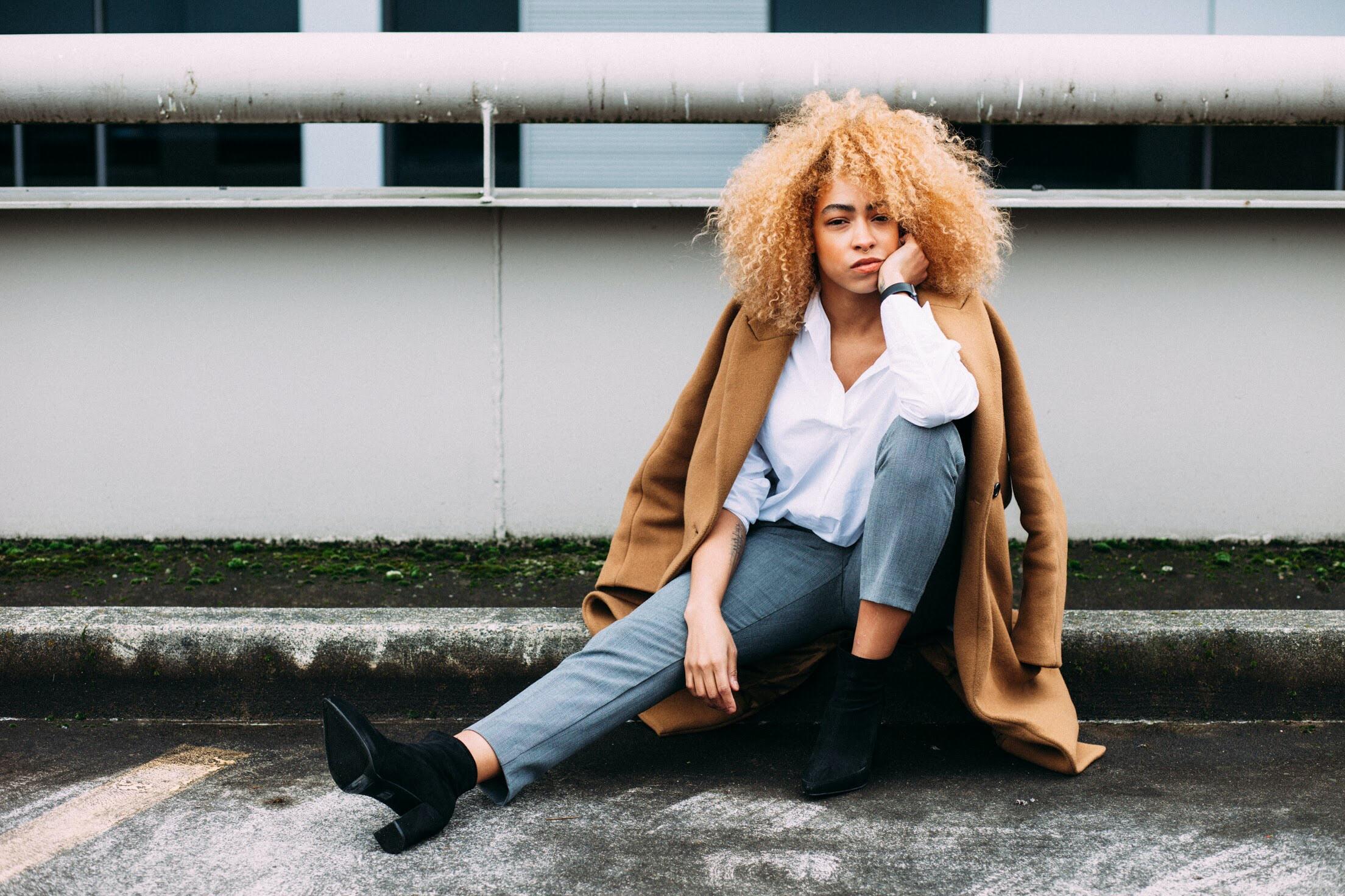 woman sitting on gray concrete pavement near white metal railing at daytime