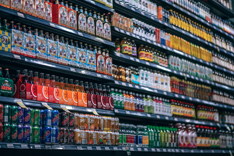 beverage bottles and cans on display shelf