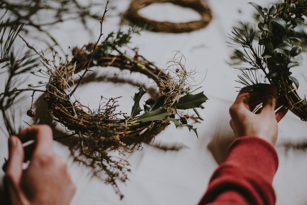 person making wreath