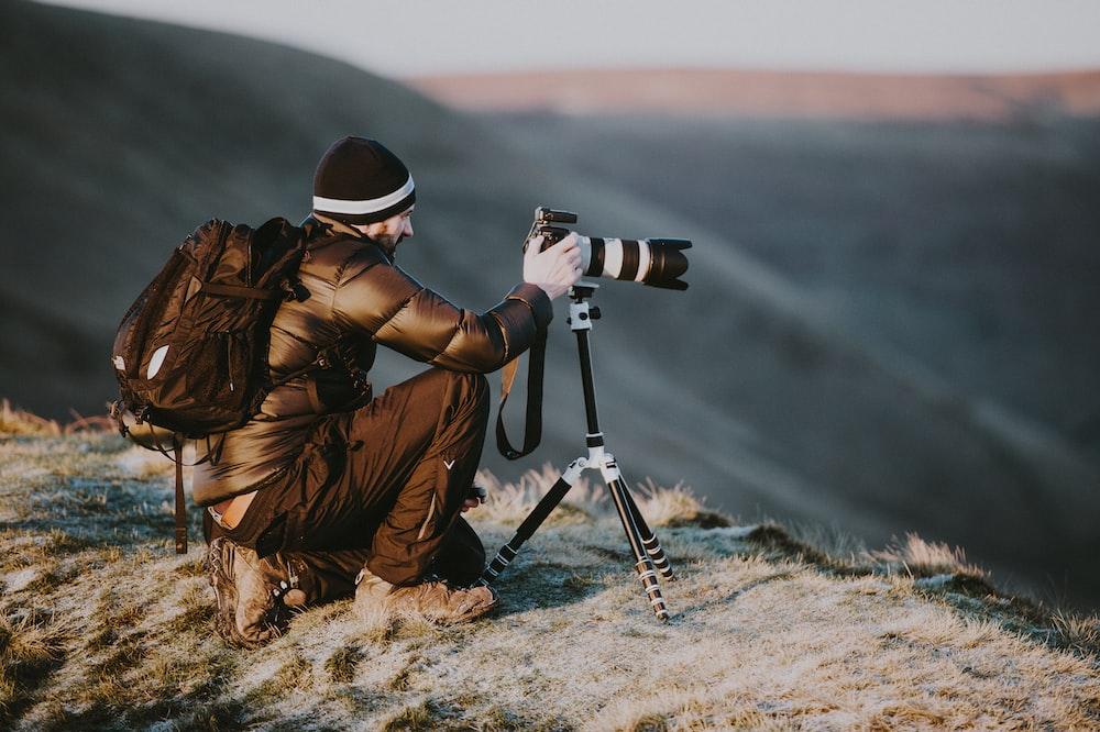 man taking photo using black and white DSLR camera on hill at daytime