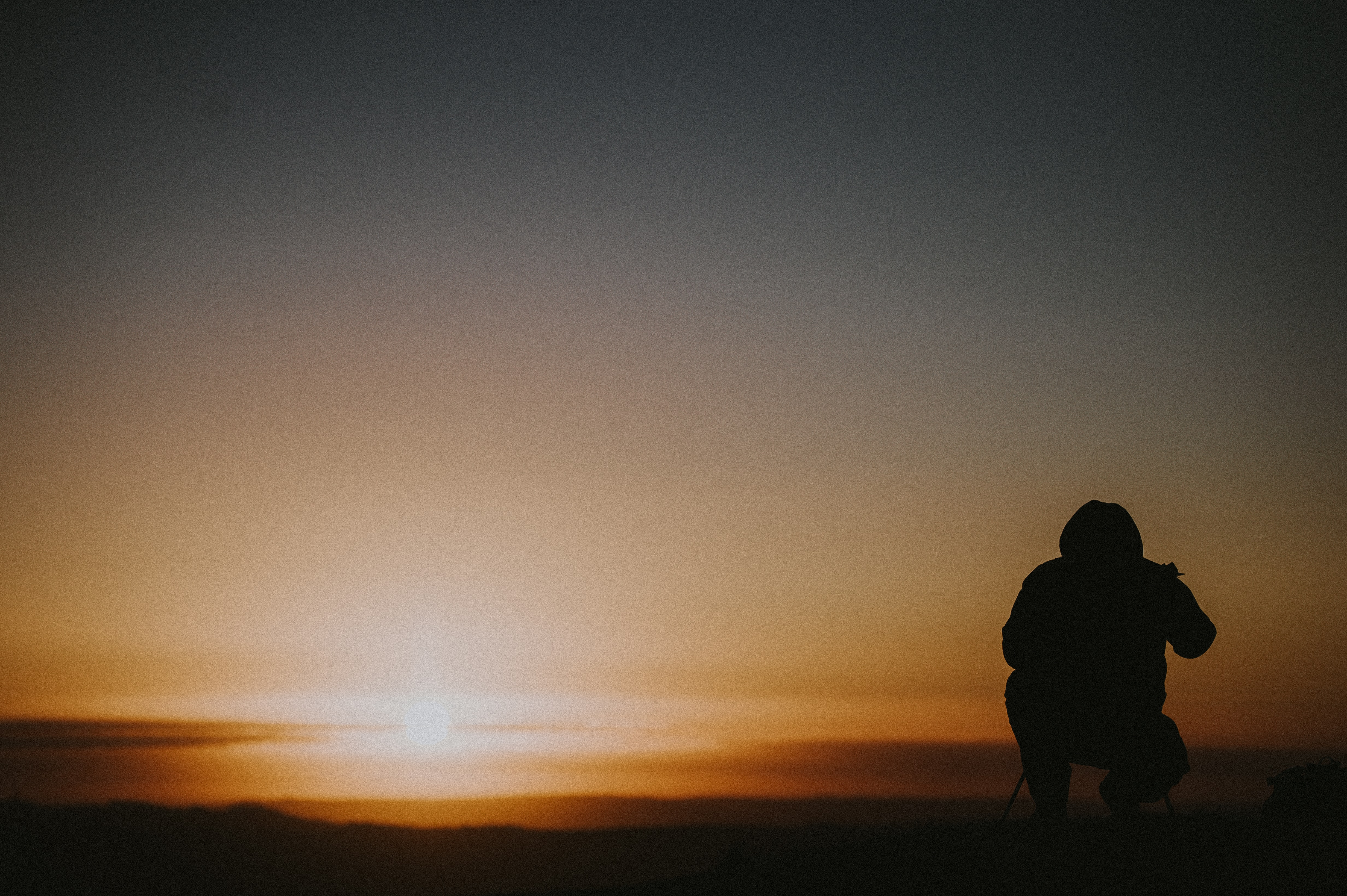 silhouette photo of person sitting under golden hour