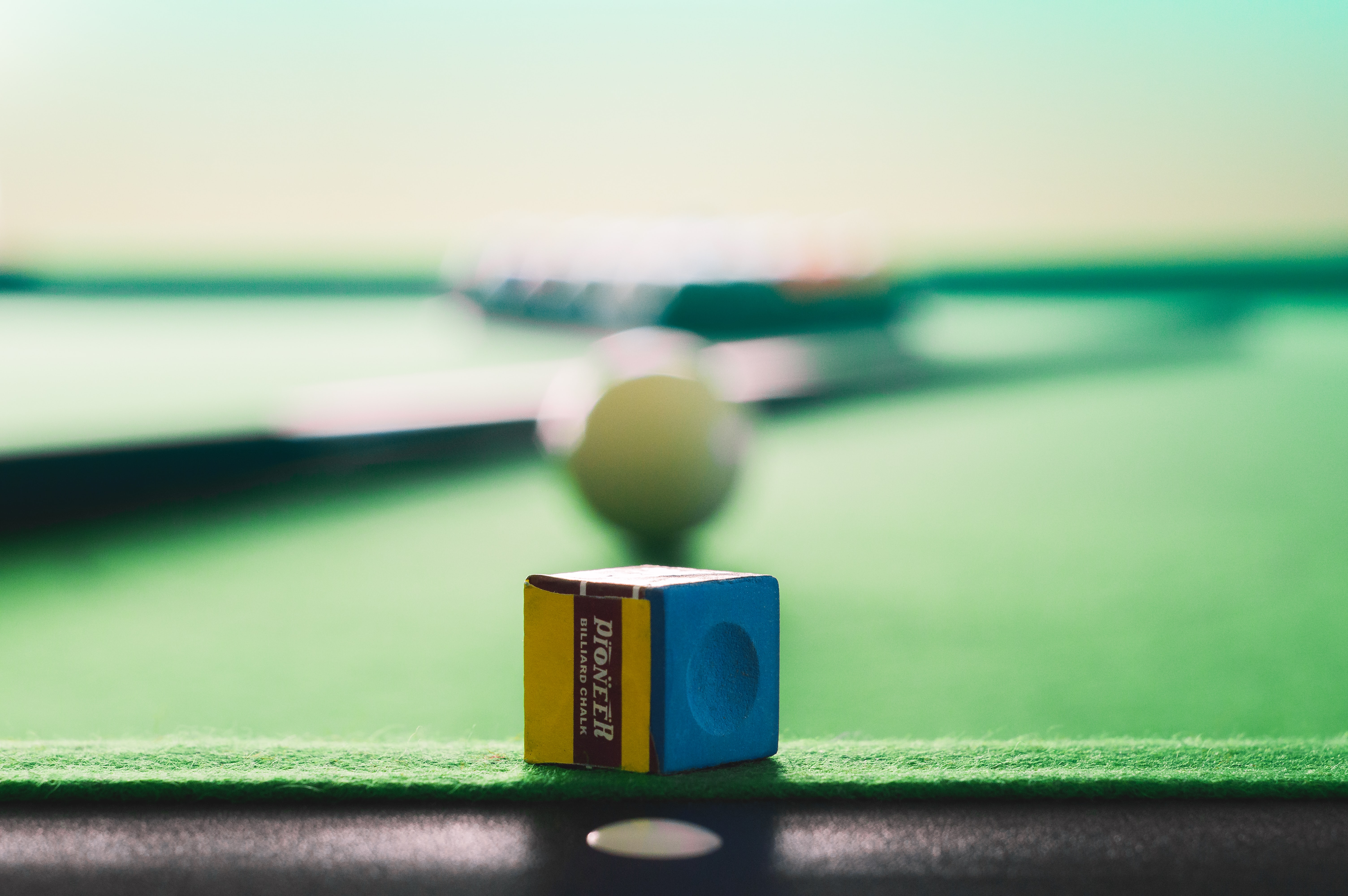 yellow and blue cue stick chalk on green and black pool table
