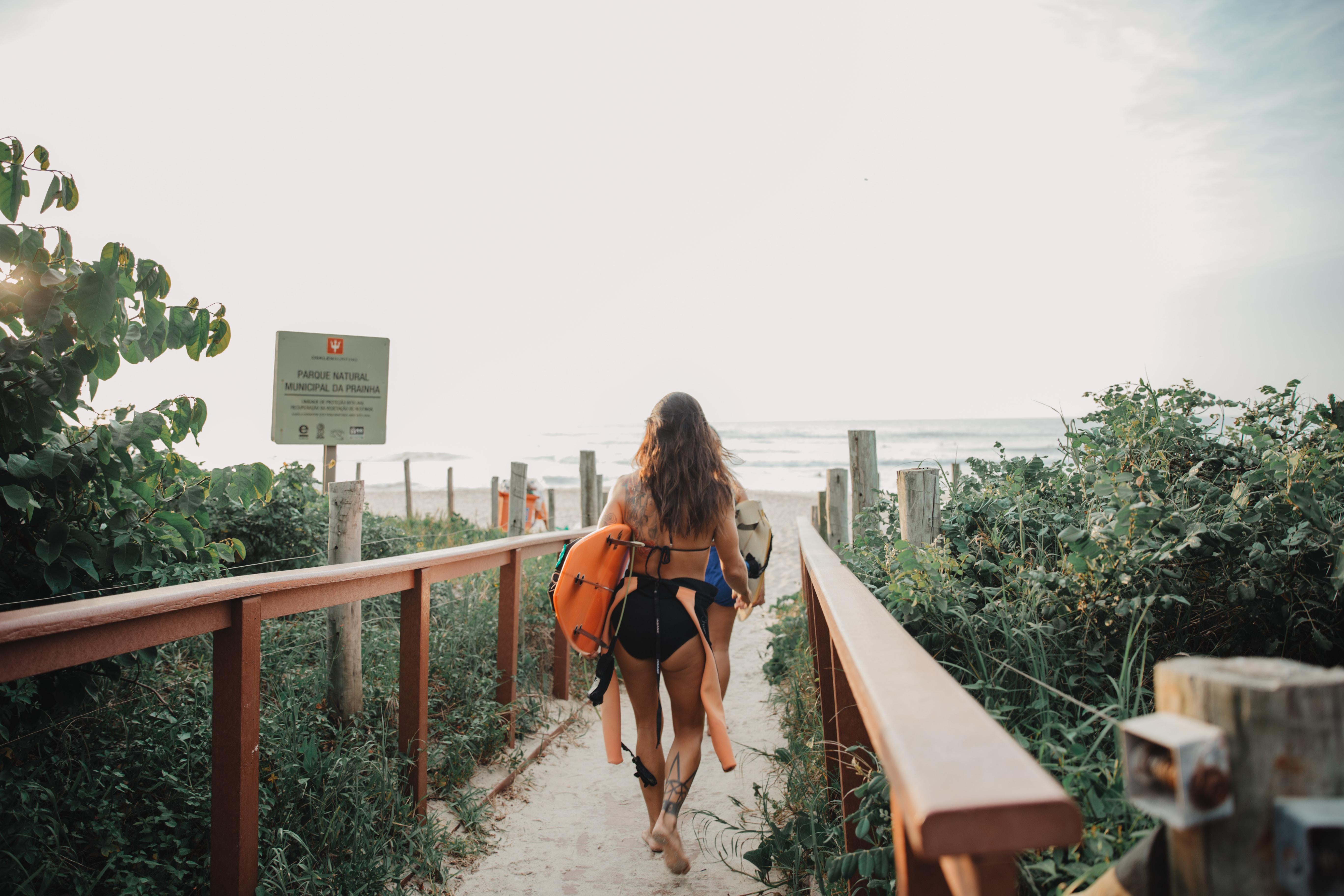 woman wearing pink and black bikini bringing orange surfboard