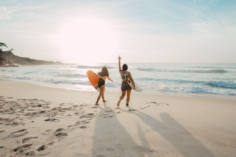 two women walking towards the ocean carrying surfboards during day