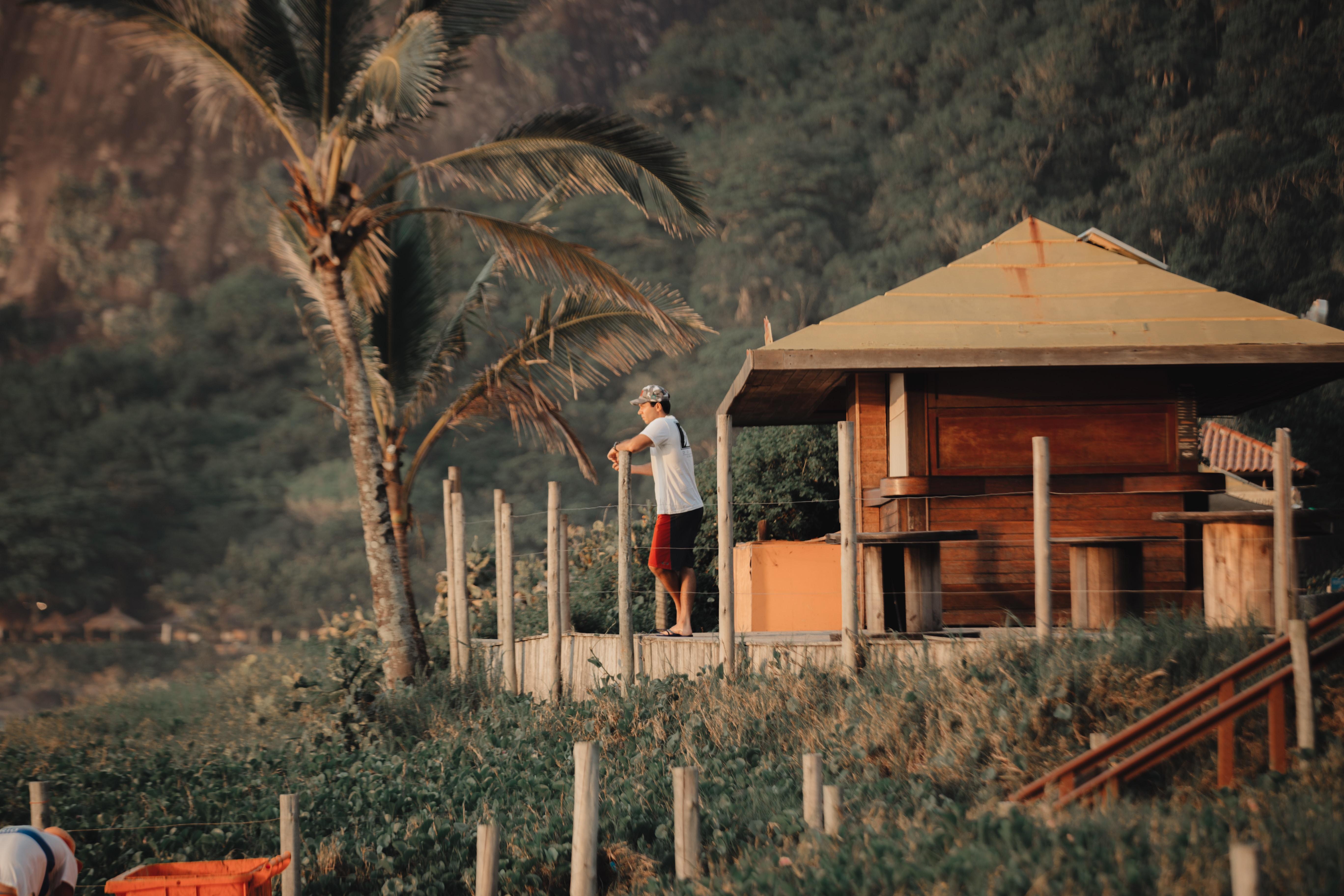 man standing on wooden hut
