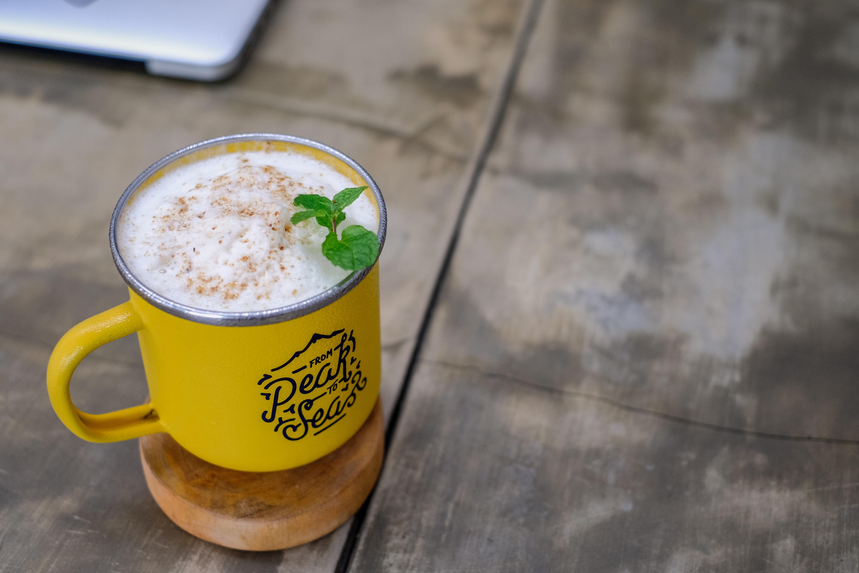 selective focus of yellow mug with white liquid