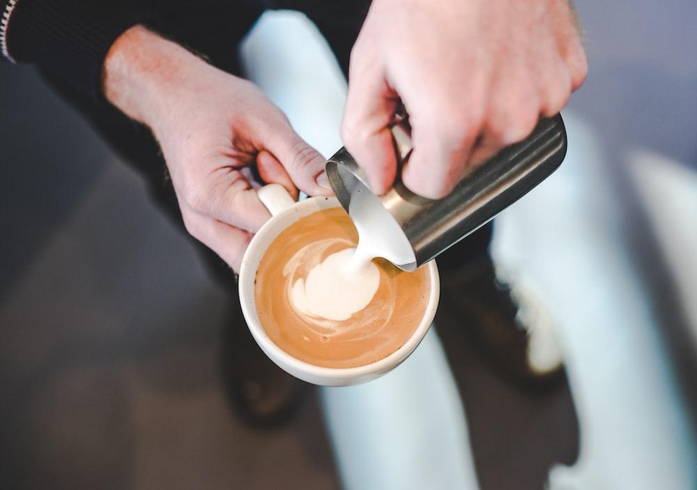 person pouring milk in coffe