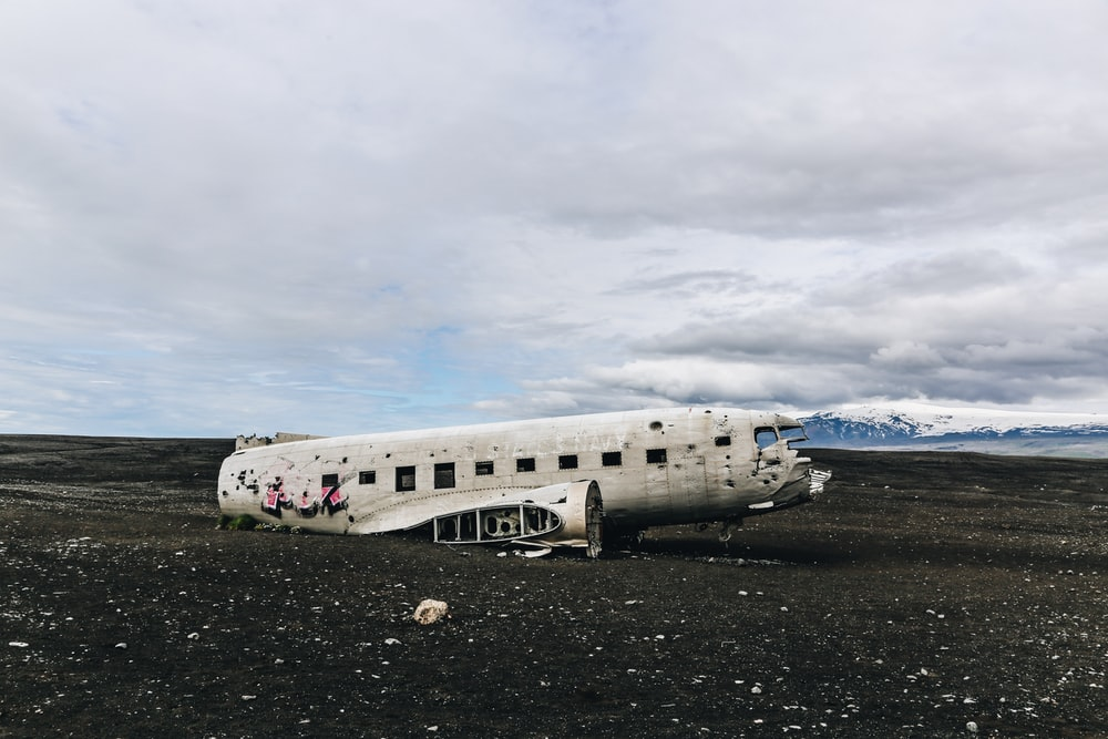 white wrecked airplane during daytime