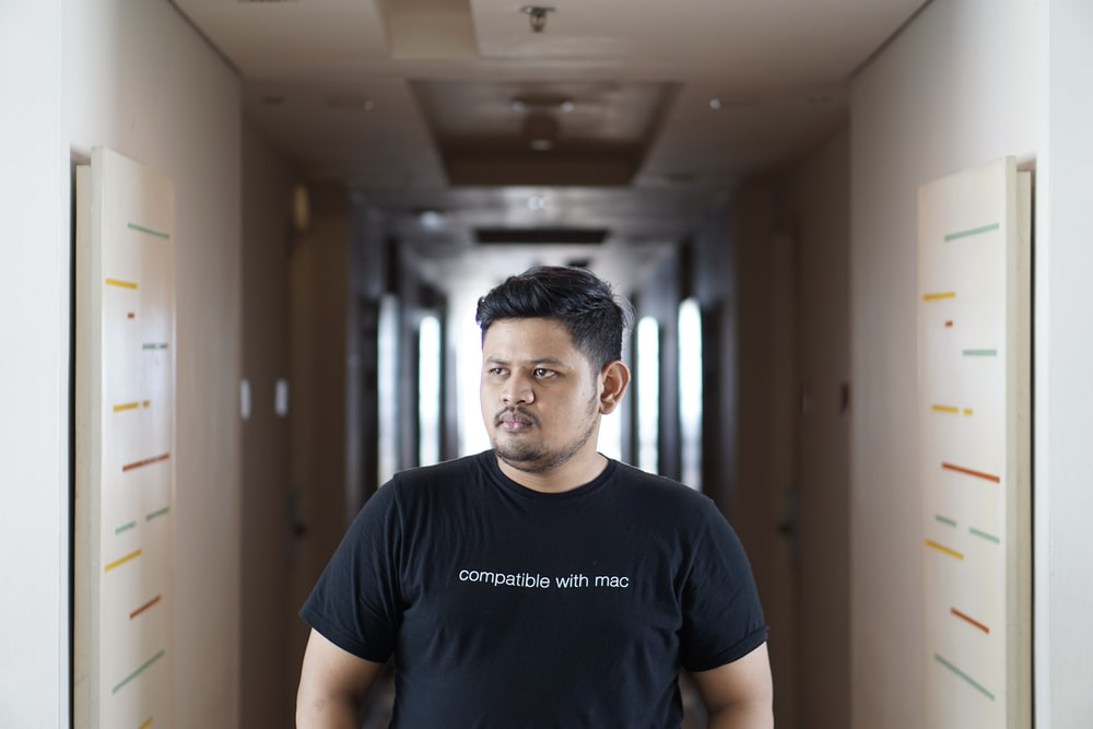 man standing in the middle of hallway