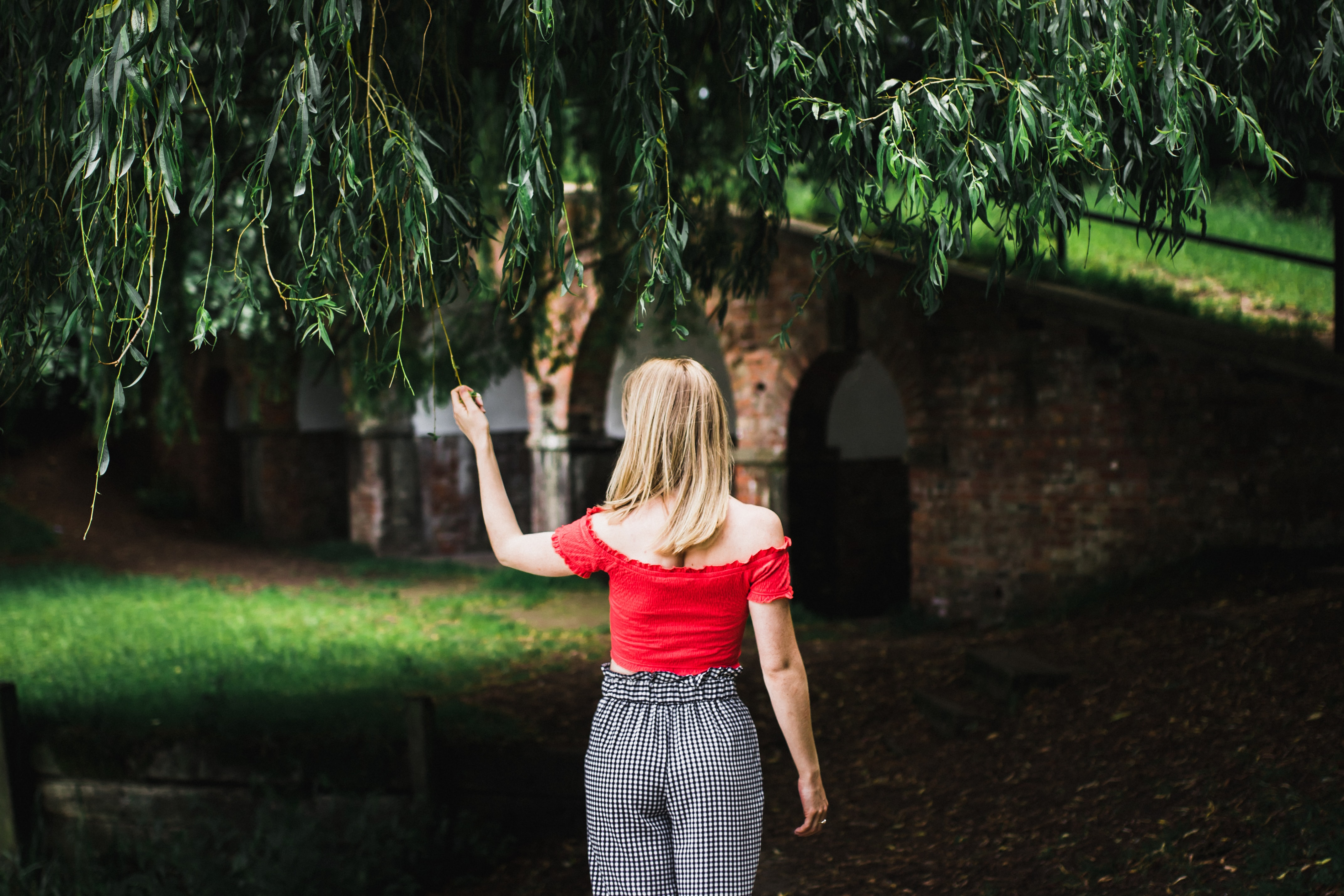 woman standing grabbing green tree leaf wearing red t-shirt