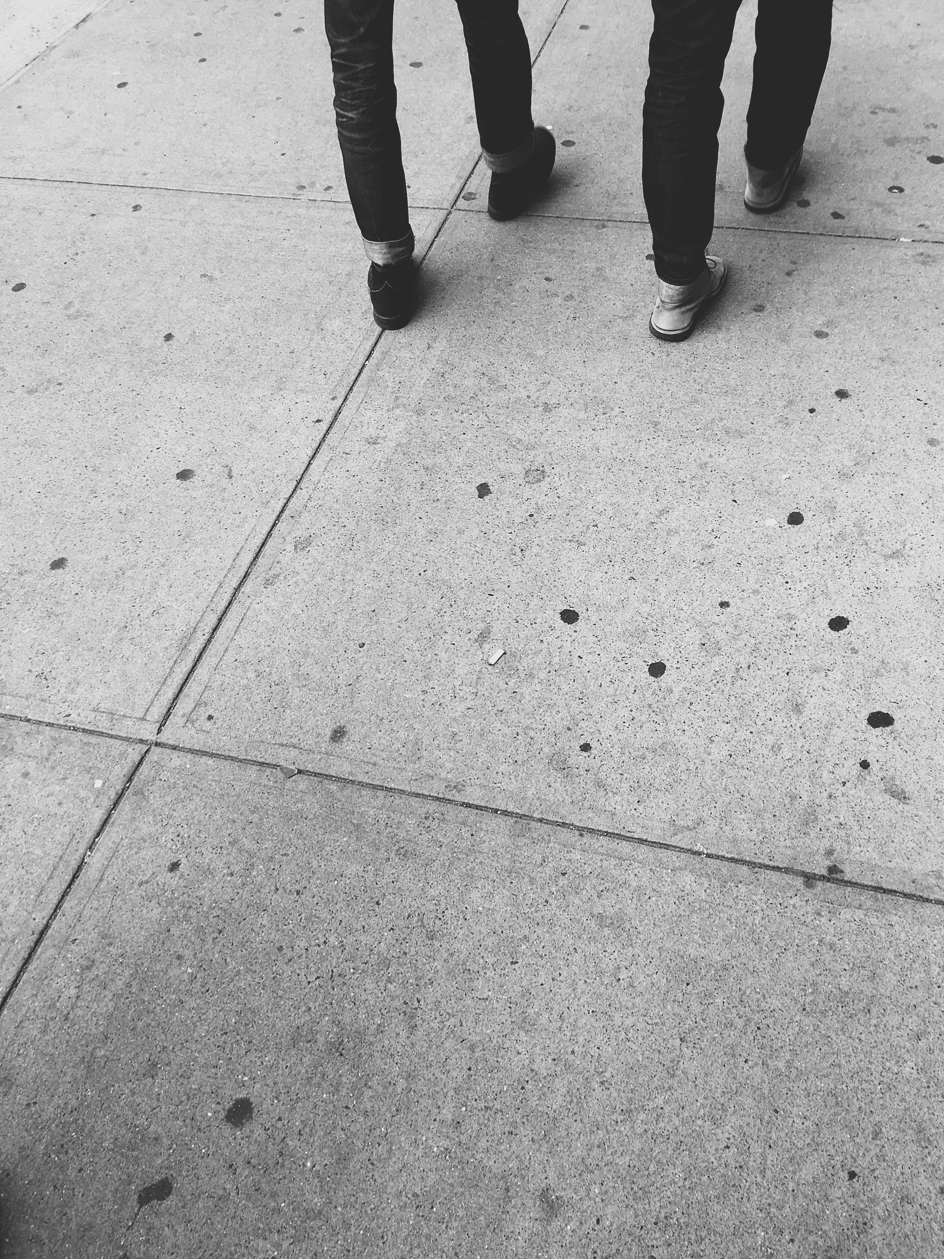 two persons walking on concrete floor