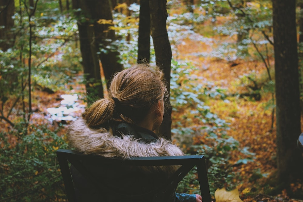 girl sitting on chair watching trees and plants