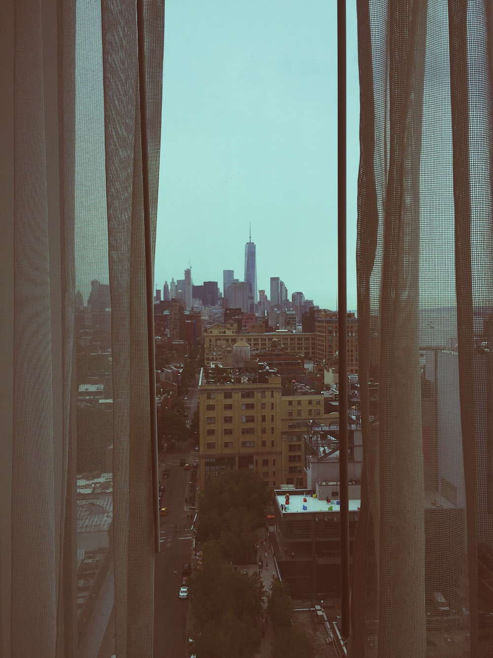 glass window with white curtains overlooking buildings and street with cityscape at distance