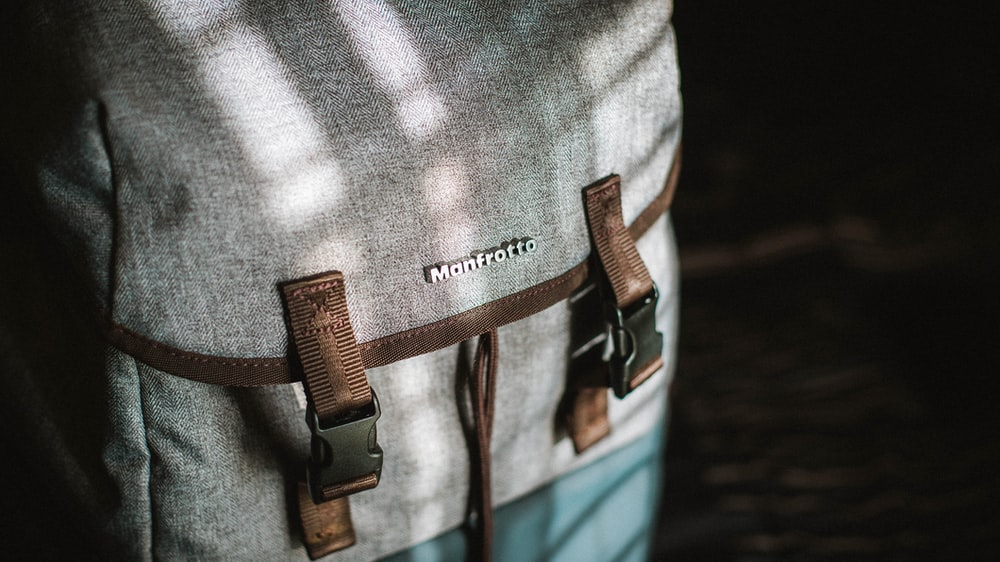 close-up photograph of gray and brown snap backpack