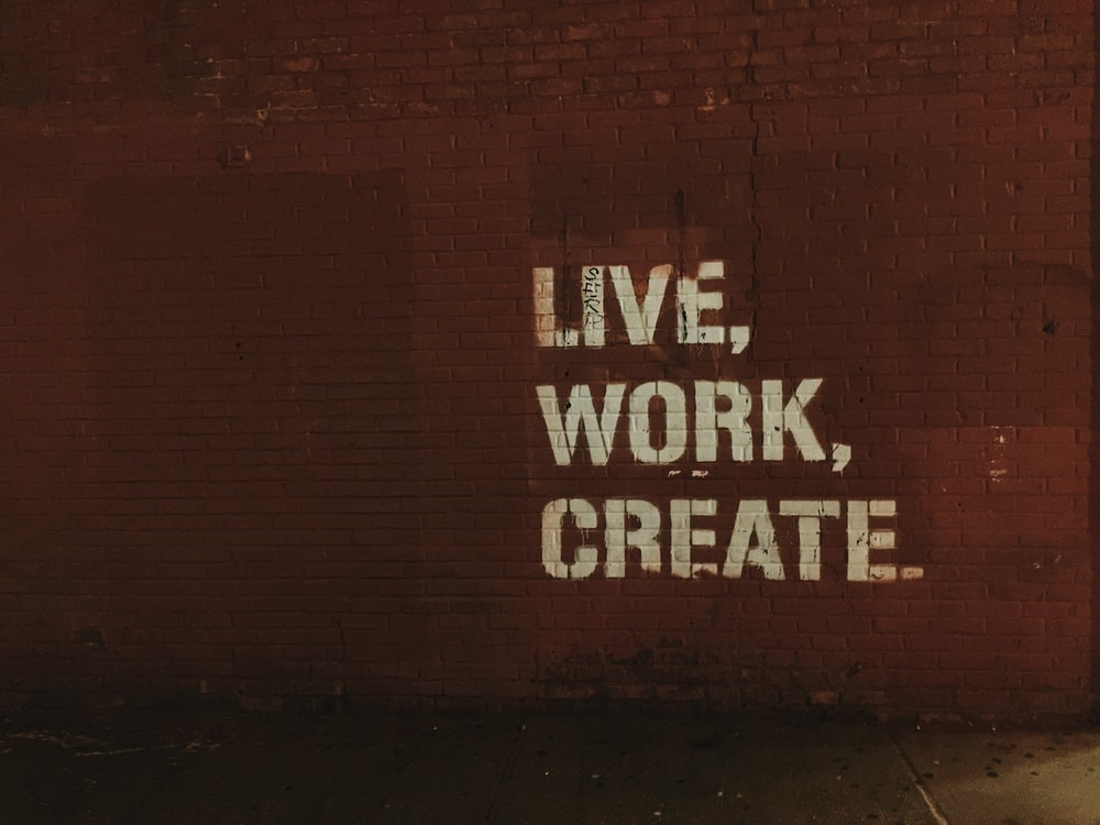 red brick wall with live, work, create. quote