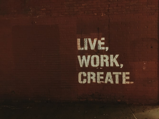 "A photo of a wall with the words ""Live, Work, Create"" stenciled on the side"