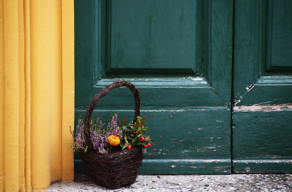 brown basket filled with flower near door