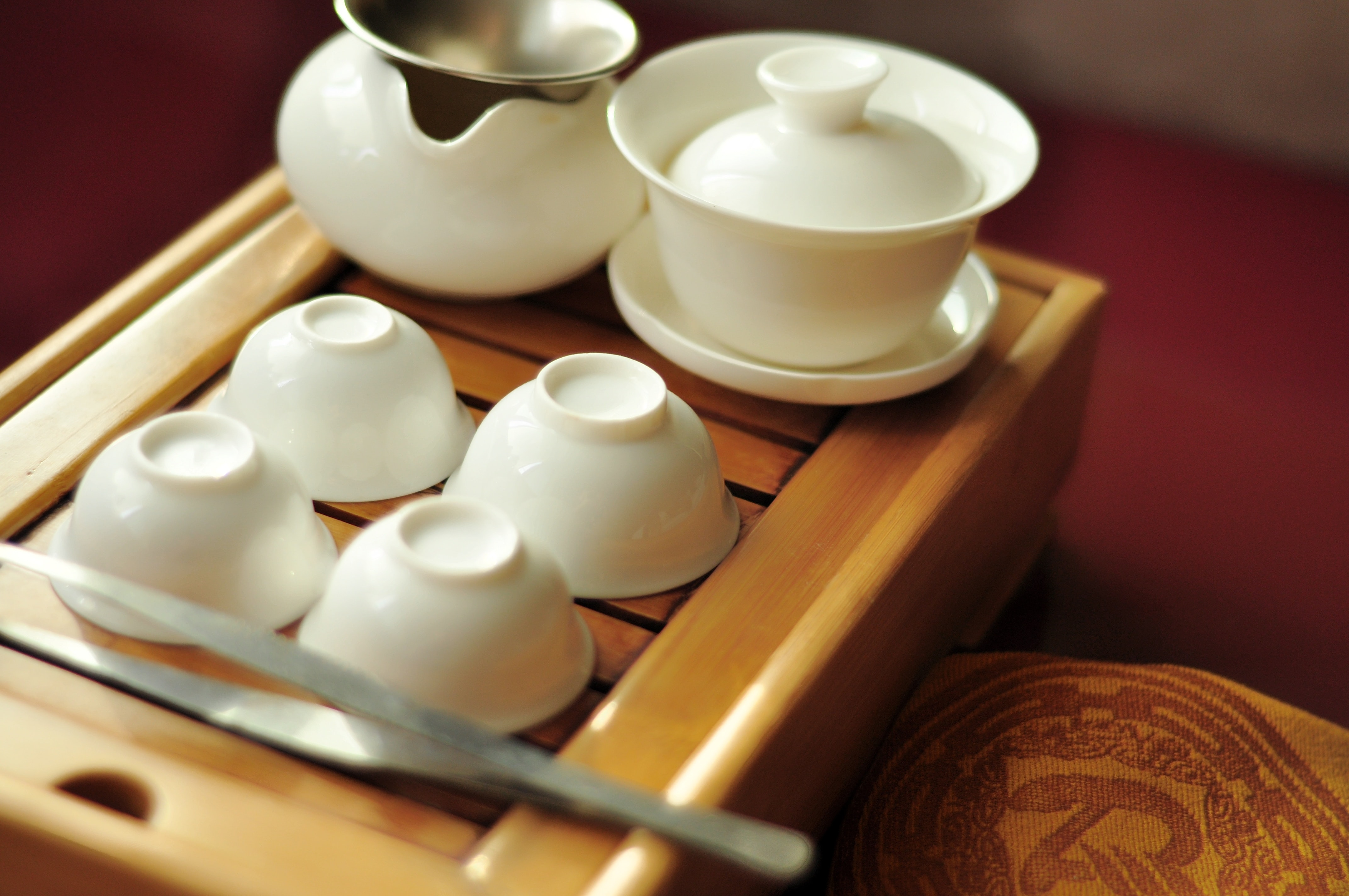 four white ceramic bowls near teapot and tureen on brown wooden tray
